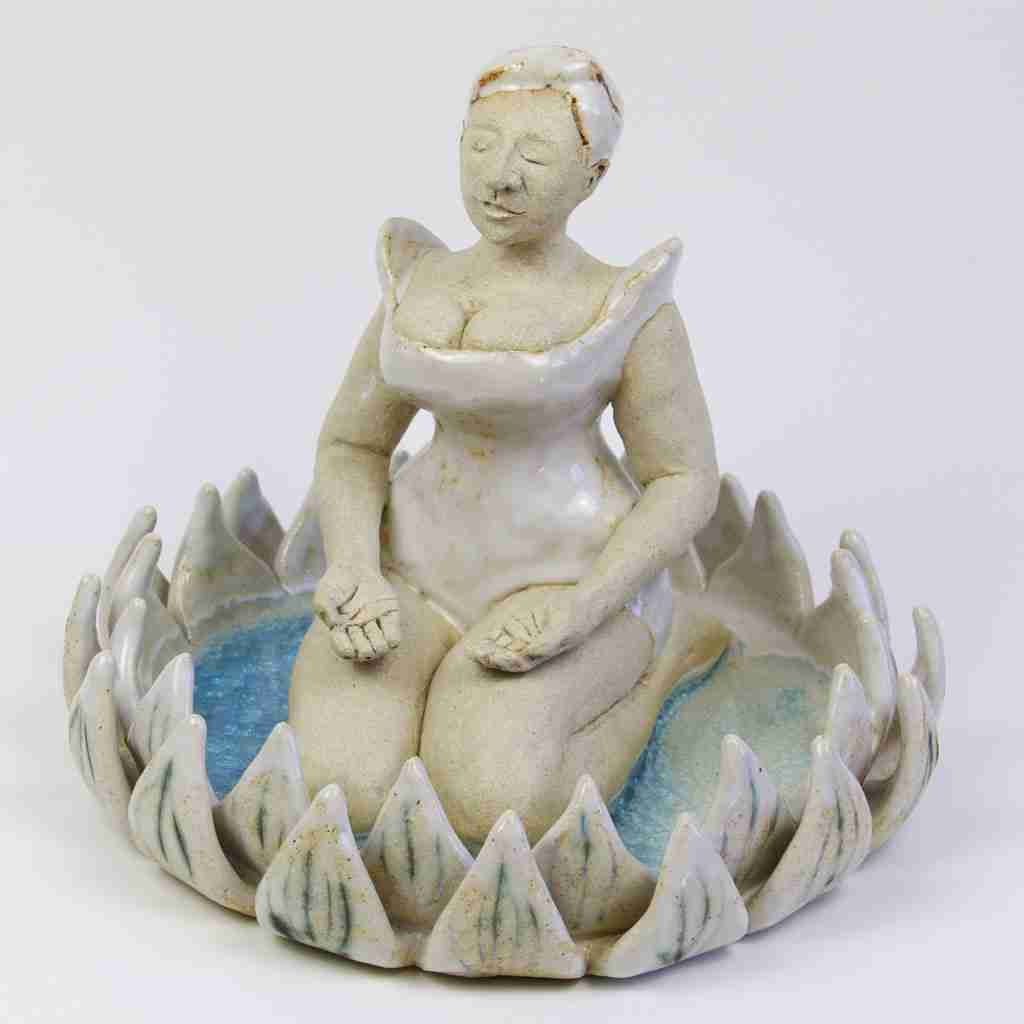 Stoneware sculpture of a lady mediating in a lotus flower